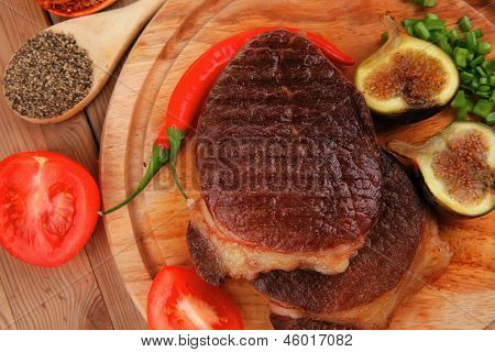 meat savory : grilled beefsteak served with hot cayenne peppers green stuff sweet figs and cutlery on wood plate over wooden table