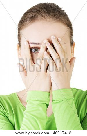 Shy or scared teenage girl peeking through covered face , isolated on white.