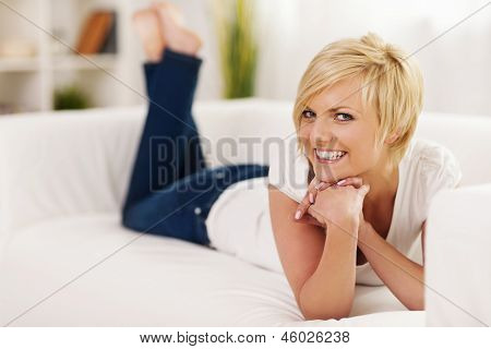 Smiling woman lying on sofa in living room