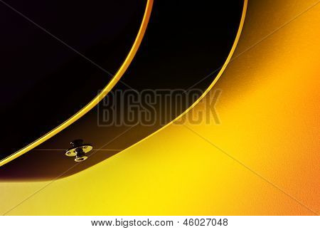 Acoustic guitar bottom close up on yellow background