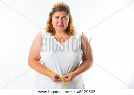 obese woman measuring her waist with tape and is unhappy