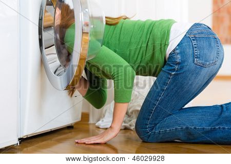 Young woman or housekeeper has a laundry day at home, she is searching for the lost socks