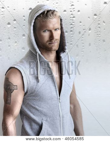 Sexy young fit man in hooded training vest against modern studio background
