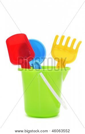 closeup of a sand / beach toy set with a pail, shovels and rake of different colors on a white background