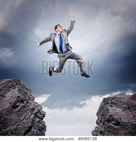 Image of young businessman jumping over gap poster