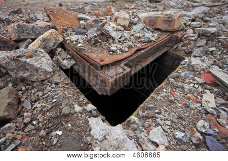 Manhole cover partially buried beneath rubble and debris. A lethal trap for the unwary. poster