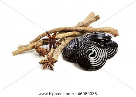 Liquorice roots, Star anise and licorice wheels on white background