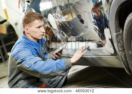 auto repairman worker in automotive industry examining car body painting or repaint at auto repair shop