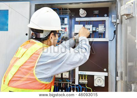 One chinese electrician builder at work with high voltage power electric line distribution fuseboard
