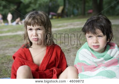 Two Little Girls Sitting On Bank Of River