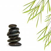Zen abstract design of black spa treatment stones in perfect balance with bamboo leaf grass over white background. poster