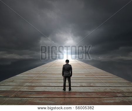 Businessman Standing On Wooden Way Face Sunlight With Cloudy Sky
