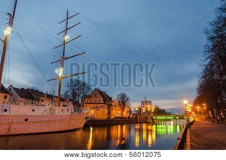 Klaipeda (Lithuania) at night. Old Town and Dane river. Ship Meridianas, 1948 - the symbol of Klaipeda city poster