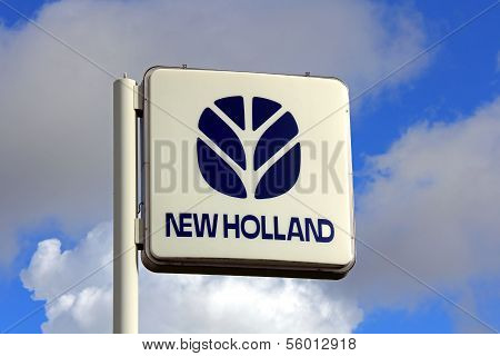 New Holland Sign Against Blue Sky With Some Clouds