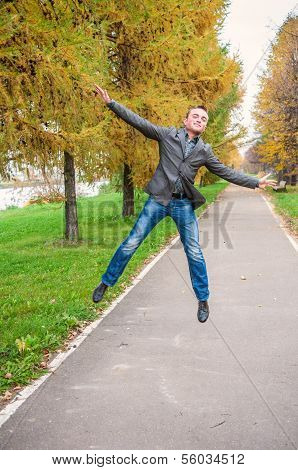 Young Man Jumping In Autumn Park