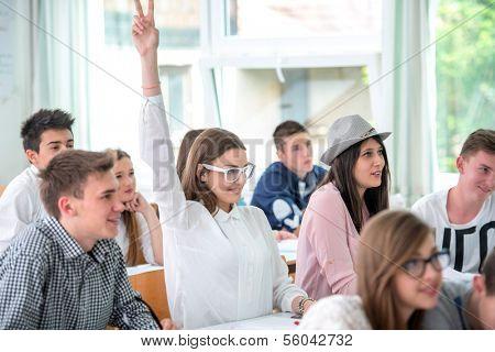 Happy schoolgirl raising hand during lecture in schoolroom