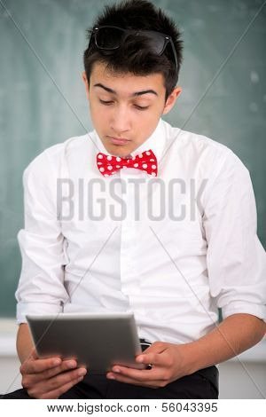 Smart looking student with tablet computer on blackboard