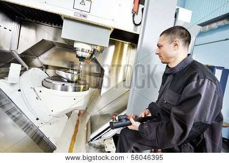 mechanical technician working at cnc milling machine center in tool workshop