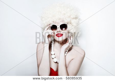 Portrait of a sexy fancy young woman smiling while wearing sunglasses and a blond wig, on grey background