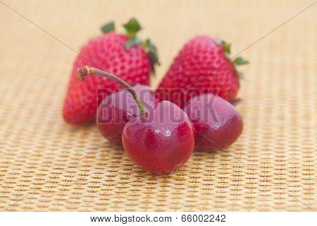 Strawberries And Cherries On Wicker Mat