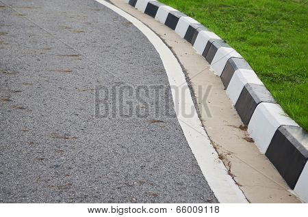 Road And Footpath With Grass.