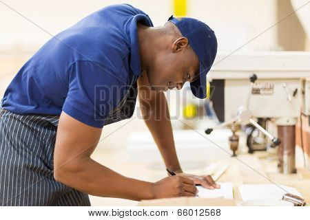 young african carpenter working in workshop