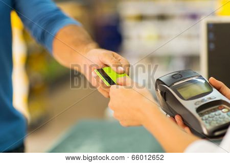 customer paying with credit card at supermarket
