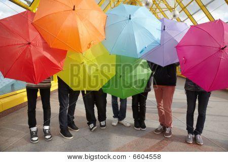 seven teens with opened umbrellas in pedestrian overpass