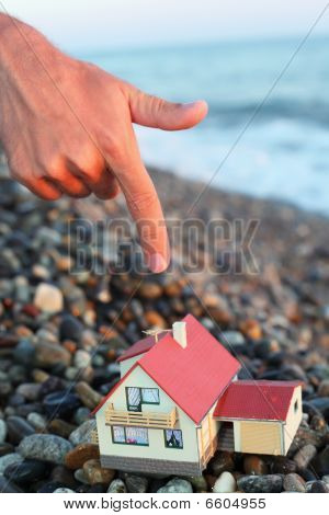 Model Of House With Garage On Stony Beach In Evening, Man's Hand With Forefinger Over House