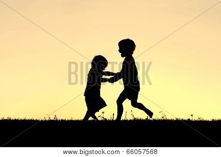 Silhouette Of Happy Little Children Dancing At Sunset