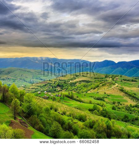 Village On Hillside Meadow With Forest In Mountain