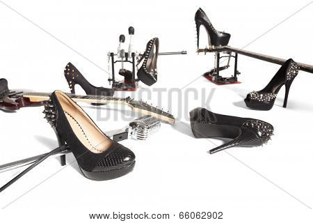 Female shoe and musical instruments scattered over white background