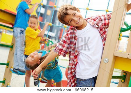 Image of cute kids having fun on playground outdoors, focus on smiling boy