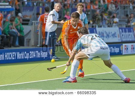 THE HAGUE, NETHERLANDS - JUNE 2 2014: Argentinian Brunet tries to block Netherlands player Kemperman lifts the ball and passes him, at the World Cup Hockey. NED beats ARG 3-1