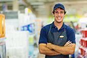 happy young salesman standing in hardware store poster