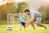 Young father with his little son playing football on football pitch poster