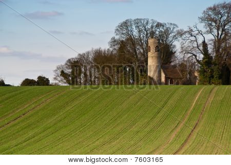 A Round-tower Church At The Top Of A Hill In The English Countryside