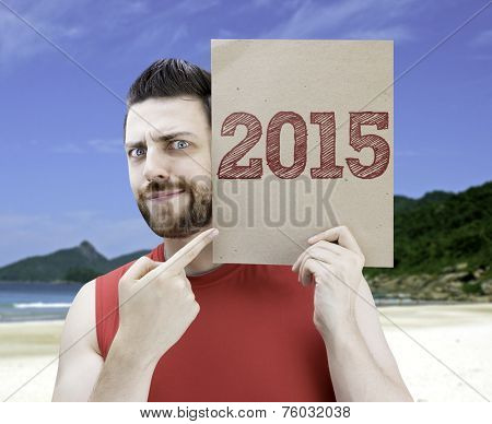 Man holding a card with the text 2015 on a beach background