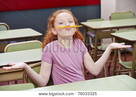 Girl doing nonsense in elementary school class with a pencil over her lips