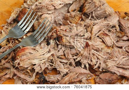 Pulled pork being shredded on wooden carving board.