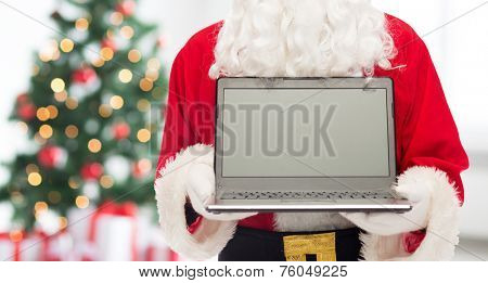 christmas, advertisement, technology, and people concept - close up of santa claus with laptop computer over living room with tree