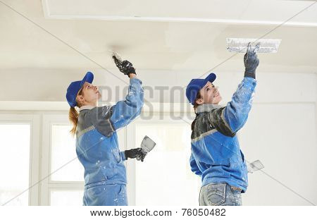 female plasterer painter at indoor ceiling renovation decoration stopping with spatula and plaster poster