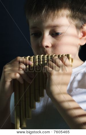 Boy Playing Panflute In Darkness