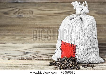 Concept of the thrift storing - Clove  in the burlap sack with the patch on a wooden background