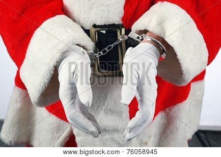 Santa in Hand Cuffs. Santa Claus has been a Bad Bad Boy this year. Perhaps he had one to many Brandy Alexander's or Too Many Cookies or went down the chimney of an Unbeliever and they called the cops.