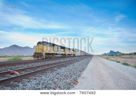 Cargo locomotive railroad engine crossing Arizona desert wilderness during early evening. poster