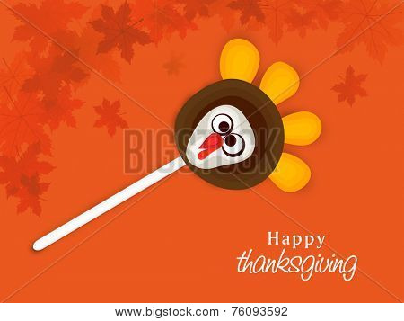 Thanksgiving Day celebration with turkey lollipop on maple leaves decorated orange background.