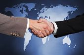 Cropped image of businessmen shaking hands against a world map. poster