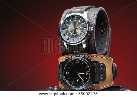 two men's watches with wide leather bracelet