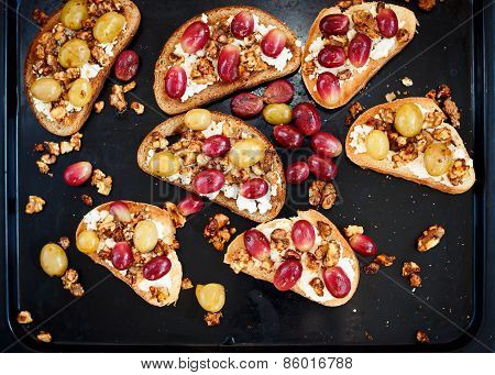 Toasts with ricotta, baked grapes, walnut on black baking, healthy sweet breakfast poster